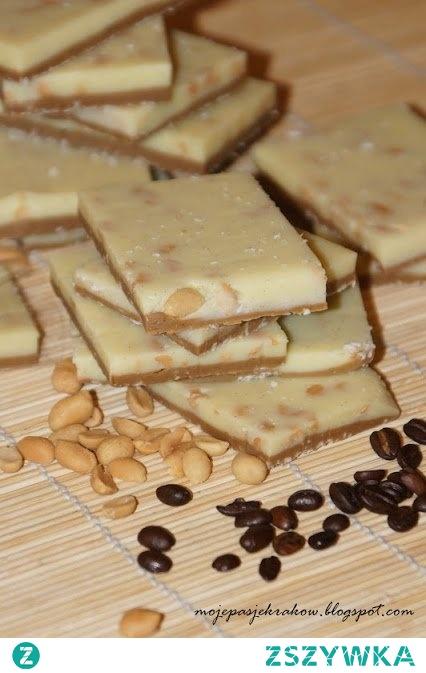 Domowa biała czekolada z kawą i orzechami  Składniki:  200g masła 1 szkl. cukru 1 szkl. śmietany 30% 400g mleka w proszku (pełne 26,5% tłuszczu) ziarenka z 1/2 laski wanilii 2 garście grubo posiekanych orzechów ziemnych 4 łyżeczki kawy rozpuszczone w małej ilości wrzącego mleka   Na małym ogniu rozpuszczamy masło, śmietanę, cukier i wanilię. Chwilę podgrzewamy do zagotowania cały czas mieszając. Zdejmujemy z ognia i powoli nie przerywając mieszania wsypujemy przesiane (!) mleko w proszku. Masa powinna być jednolita i bez grudek. Gdyby jednak takowe powstały należy całość przetrzeć przez sito. (ja robiłam w termomixie. Dosypywałam mleko cały czas miksując (temp80/obr.5). Z masy odłożyć 1/3 i dodać do niej rozpuszczoną kawę - dobrze wymieszać. Do pozostałych 2/3 masy dodać orzechy i również wymieszać. Masę białą rozsmarować na blaszce wyłożonej papierem do pieczenia (33x23). Jeśli jest już mocno gęsta można sobie pomóc wałkując ją przez folię. Na niej rozsmarować masę kawową (ja dodatkowo posypałam ją jeszcze kokosem, ale nie jest to konieczne). Odstawić do stężenia. Kroić w kwadraty dowolnej wielkości i pakować np w ozdobne paczuszki z celfanu :) Czekolada doskonale się nadaje również do zamrożenia w woreczkach. Gdy najdzie nas ochota na coś słodkiego wystarczy wyjąć kawałeczek :) Czekolady wychodzi naprawdę sporo :) Zważyłam ją i wyszło mi 1077 g