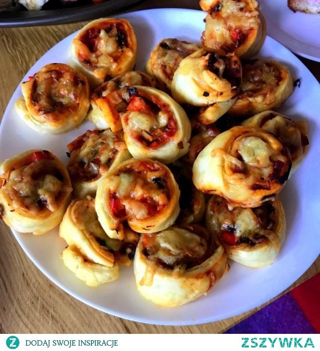 Pizzerinki z ciasta francuskiego.  Składniki:  ciasto francuskieprzecier pomidorowy1/2 cebuli4-5 dużych pieczarek3-4 plastry szynki3-4 plastry sera1/3 papryki  Sposób wykonania: Składniki są dowolne. Ja używam tego co się dobrze ze sobą komponuje, i zwykle znajduje miejsce w mojej lodówce.  Ciasto francuskie rozkładamy i smarujemy przecierem pomidorowym (dość obficie, aby ciasto nie było suche). Pieczarki kroimy w drobną kostkę i podsmażamy na odrobinie margaryny, do puszczenia soku. Doprawiamy je solą i pieprzem. Na ciasto wysypujemy drobno skrojoną cebulę, szynkę, paprykę i odcedzone z wody którą wypuściły – pieczarki. Całość zawijamy bez sera. Jeżeli nie będziemy ich piec od razu (Najlepsze są świeże z piekarnika), to zawijamy roladę w papier i wstawiamy do lodówki.  Przed włożeniem do piekarnika, kroimy roladę w plastry (nie za cienkie, bo się rozpłyną pod wpływem temperatury) ok. 3-4 cm. Górę pizzerinek posypujemy obficie żółtym serem, i wykładamy na papier do pieczenia. Piekarnik nagrzewamy do 200 stopni i pieczemy ok 15-20 min do zarumienienia ciasta. Idealne z sosem czosnkowym, lub pesto bazyliowym.