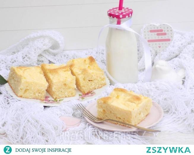 Ciasto jogurtowe z białym serem  Ser: 25 dag sera białego półtłustego 2 łyżki cukru 1 cukier waniliowy 1 budyń waniliowy 1 jajka 4 kopiaste łyżki wiórków kokosowych  Ciasto: 2 jajka półtorej szklanki mąki tortowej pół szklanki mąki krupczatki pół szklanki cukru 2 cukry waniliowe 100 ml oleju 20 dag jogurtu naturalnego 2 płaskie łyżeczki proszku do pieczenia   Masa serowa: Do miski wbijamy jajko, dodajemy oba cukry, dodajemy ser i miksujemy blenderem ręcznym na gładką masę, następnie wsypujemy budyń i chwilę miksujemy, na koniec wsypujemy wiórki kokosowe i dokładnie mieszamy. 2. Ciasto: Jajka wbijamy do miski, wsypujemy oba cukry i miksujemy na puszystą masę, następnie wlewamy olej i chwilę miksujemy, dodajemy jogurt naturalny i dalej miksujemy. Na koniec wsypujemy mąkę krupczatkę, mąkę tortową i proszek do pieczenia, miksujemy do dokładnego połączenia się składników. 3. Do pieczenia: Ciasto wykładamy na blaszkę o wymiarach około 25 cm x 21 cm wyłożonej papierem do pieczenia, na ciasto kupkami wykładamy masę serową. 4. Pieczenie: Ciasto pieczemy w temperaturze 180 stopni do zrumienienia przez około 45-50 minut. Ciasto sprawdzamy suchym patyczkiem czy jest upieczone. Upieczone studzimy. 5. Podanie: Gotowe ciasto kroimy i podajemy.   Szklanka do odmierzania składników o pojemności 250 ml. Blaszka o wymiarach około 25 cm x 21cm. Ciasto można pokroić na około 12 dużych kawałków. Ciasto można upiec w tortownicy o średnicy 23 cm.