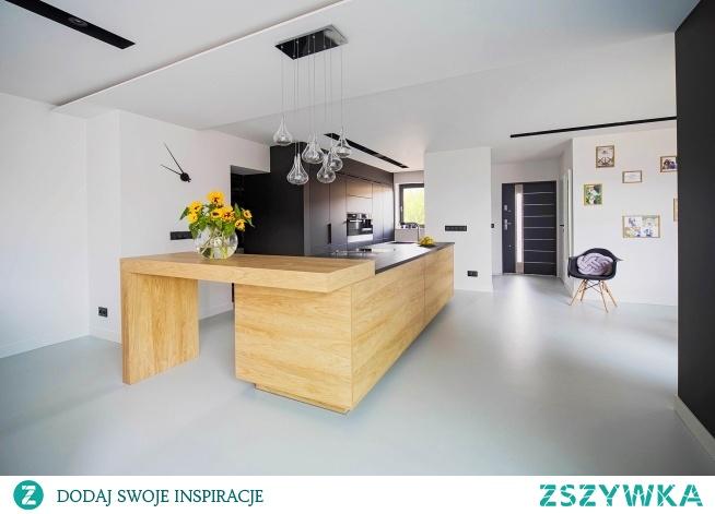 Czerń, drewno i biel, to klasyczne i minimalistyczne połączenie wspaniale prezentuje się na dużej przestrzeni. Otwarta na salon kuchnia utrzymana w minimalistycznym stylu idealnie wkomponowuje się w styl całego domu.