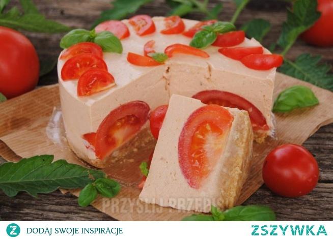 Pomidorowy tort  Tortownica o średnicy 16 cm Spód • Około 150 g krakersów,, • 75 g stopionego masła, • 20 g utartego parmezanu, • Sól pieprz do smaku Nadzienie: • 2 jajka, • 400 g sera białego, • 3 płaskie łyżeczki żelatyny, • 150 ml śmietany, • 1,5 pomidora do środka tory, • Mały koncentrat pomidorowy, • 1 mała cebula, • 1 -2 ząbki czosnku, • Sól, pieprz do smaku, • Listki bazylii do dekoracji, • 3 pomidorki koktajlowe do dekoracji    Spód: Krakersy kruszymy. Dokładamy do nich masło, ser, Dokładnie mieszamy i doprawiamy do smaku. Masą wykładamy dno tortownicy, dobrze przygniatamy i odstawiamy do lodówki. Między czasie przygotowujemy nadzienie. Zalewanie masy serowej2. Żelatynę rozpuszczamy w około 1/3 szklanki wody. Studzimy. Cebulkę wraz czosnkiem obieramy i kroimy w kostkę. Do malaksera (robota kuchennego) przekładamy ser, żółtka, cebulę, czosnek, koncentrat oraz śmietanę. Całość miksujemy na gładką masę. Doprawiamy do smaku, wg swoich gustów. Między czasie ubijamy białka. Do zmiksowanej masy dokładamy ubite białka. Delikatnie mieszamy. Następnie dokładamy żelatynę. Dokładnie mieszamy. Pomidory przeznaczone do środka kroimy na ćwiartki. Połowę masy serowej wylewamy na krakersowi spód. Układamy na niej pokrojone pomidory. Zalewamy je pozostała masą. Torcik odstawiamy na około 3-4 godziny do lodówki.  Przed podaniem dekorujemy pokrojonymi pomidorami koktajlowymi oraz listkami bazylii