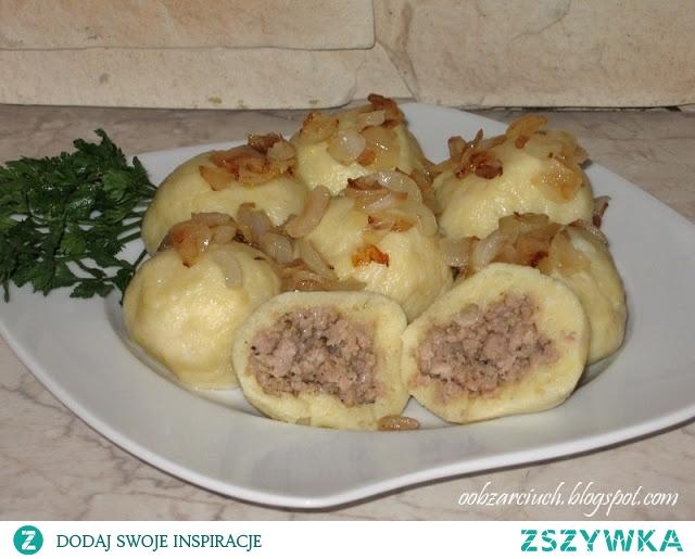 Knedle z mięsem mielonym 28 sztuk ciasto: 1 kg ziemniaków ok. 30 dag mąki pszennej 1 duże jajko lub 2 małe farsz: 40 dag mięsa mielonego np. od łopatki lub innego 2 małe cebule 1 jajko 2 łyżki bułki tartej 2 ząbki czosnku pieprz mielony majeranek sól Ziemniaki gotujemy w lekko osolonej wodzie. W międzyczasie przygotowujemy farsz: cebulę drobno kroimy i podsmażamy ją na złoty kolor. Do surowego mięsa dodajemy majeranek, pieprz, sól i czosnek przeciśnięty przez praskę. Mieszamy, wrzucamy do podsmażonej cebuli i smażymy ok. 10 minut. Następnie odstawiamy do wystudzenia, dodajemy jajko i bułkę tartą. Wszystko jeszcze raz dokładnie mieszamy. Ugotowane i wystudzone ziemniaki mielimy w maszynce do mięsa lub przeciskamy przez praskę. Do ziemniaków dodajemy mąkę i wbijamy jajko. Potem zagniatamy ciasto. Z ciasta formujemy wałek i kroimy go na małe porcje ok. 3/4 cm. Z każdego kawałka robimy dłonią placuszek i po środku nakładamy wcześniej powstały farsz. Zlepiamy i formujemy kulkę. Knedle wrzucamy do osolonego wrzątku i gotujemy ok. 3 minut od wypłynięcia na powierzchnię. Knedle podajemy bezpośrednio po wyjęciu z wody, z podsmażoną cebulką, skwarkami lub z sosem np. grzybowym.