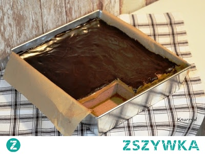 Ciasto MARS bez pieczenia        forma 36x21 cm  Spód:      ok. 14 szt. kakaowych herbatników   I warstwa:       1 l śmietanki 30%      4 łyżki cukru pudru     3 łyżki ciemnego kakao     50 g orzeszków ziemnych niesolonych     4 łyżki żelatyny     1/2 szklanki wrzątku   II warstwa:      1 puszka masy kajmakowej (krówkowej) ok. 400 g   Polewa:      4 łyżki wody lub mleka     3 łyżki cukru pudru     3 łyżki ciemnego kakao     100 g margaryny (lub masła)     2  płaskie łyżeczki mleka w proszku  . Formę wyłożyć papierem do pieczenia, na dnie ułożyć herbatniki.  2. Żelatynę rozpuścić dokładnie w 1/2 szklanki wrzątku. Pozostawić do całkowitego ostygnięcia. Orzeszki utrzeć na gładką masę (np. młynkiem do kawy).  3. Śmietankę 30% ubić mikserem (lekko zacznie się pienić), dosypać cukier puder i kakao, zmiksować. Dolać powoli ostudzoną żelatynę (cały czas miksując), a na koniec utarte orzeszki. Chwilę miksować do uzyskania jednolitej masy.  4. Masę wyłożyć na herbatniki. Wstawić na kilka minut do lodówki, tam szybko zacznie tężeć.  5. Gdy I warstwa wystarczająco stężeje, rozsmarować na niej warstwę z masy krówkowej.  6. Przygotować polewę: w rondelku zagotować 4 łyżki mleka lub wody, dosypać cukier puder i rozpuścić. Dodać margarynę. Gdy się rozpuści, zdjąć rondelek z ognia i dodać przesiane przez sitko kakao. Wymieszać szybko i dokładne. Następnie dodać mleko w proszku i jeszcze raz dobrze wymieszać. Jeśli polewa wydaje się za gęsta, dodać odrobinę mleka.  7. Polewę wylać na masę krówkową. Całość włożyć do lodówki do całkowitego stężenia. Najlepiej podawać schłodzone.