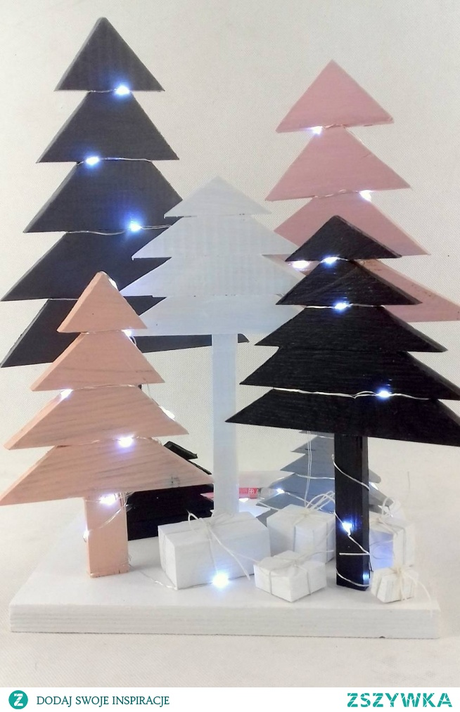 Drewniana instalacja składająca się z 7 choinek .  Choinki ze sklejki sosnowej pomalowane kolorową i bezbarwną farbą akrylową. Światełka LED (50) na metalowym druciku na baterie. Choinki różnej wysokości