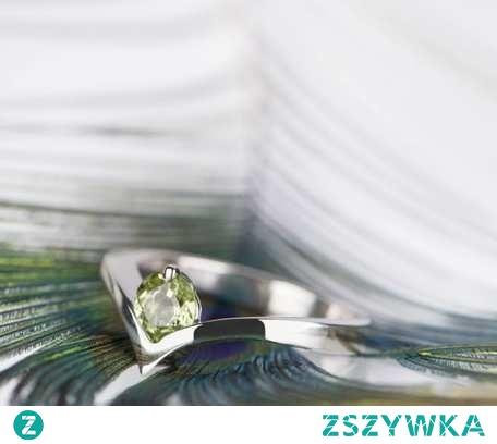 Srebrny pierścionek zaręczynowy z perydotem - pięknym naturalnym zielonym kamieniem. Perydoty są dość jasnymi kamieniami o stonowanym kolorze. Nie oznacza to jednak że kamień jest mdły i nieciekawy - kamienie, które zamawiam u stałego dostawcy charakteryzują się zawsze piękną brylancją, mienią się i błyszczą w świetle. Perydot to kamień urodzinowy sierpnia, dlatego pierścionek będzie nie tylko nadawał się na zaręczyny, ale również stanowi dobry wybór na prezent urodzinowy dla osoby urodzonej w ostatnim miesiącu wakacji.