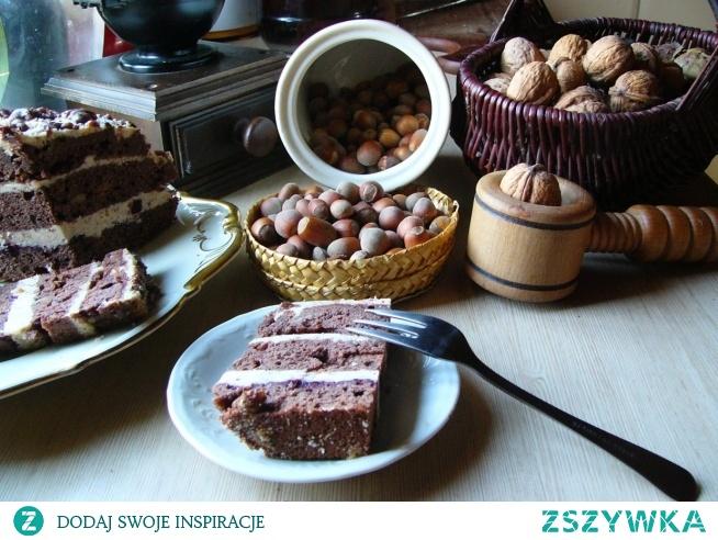 Murzynek z masą orzechową  NA CIASTO:      margaryna     25 dag     jajka     4 sztuki     cukier     1 szklanka     woda     0.5 szklanki     mąka     2 szklanki     proszek do pieczenia     2 łyżeczki     kakao     3 łyżki     orzechy siekane     3 łyżki  NA MASĘ ORZECHOWĄ:      orzechy laskowe mielone     0.5 szklanki     orzechy włoskie     0.5 szklanki     masło 82%     25 dag     cukier     0.5 szklanki     mleko     1 szklanka  DODATKOWO:      dżem kwaśny     0.5 szklanki  Do garnka wlać wodę, dodać cukier, margarynę i kakao, postawić na gazie i podgrzać do połączenia się składników. Odlać 0,5 szklanki masy, a po ostudzeniu wymieszać ją z mąką, proszkiem do pieczenia i posiekanymi orzechami. Ciasto przełożyć do tortownicy i piec 40-45 minut w 180 st.C. Po ostudzeniu ciasto pokroić na 3 krążki.  Masa: Do rondla wlać szklankę mleka i zagotować, wsypać zmielone orzechy, wymieszać i odstawić do wystudzenia. Masło utrzeć z cukrem na puch, ciągle ucierając dodawać namoczone orzechy , stopniowo po 1 łyżce. Spód ciasta posmarować dżemem, ja użyłam jabłkowo-aroniowego. Na dżem wyłożyć masę, rozsmarować, przykryć ciastem i ponowić czynność. Wierzch ciasta również posmarować masą. Wierzch ciasta po schłodzeniu skropić odlana masą.  Gdyby namoczone orzechy były bardzo rzadkie, dosypujemy do mleka 2 łyżki mielonych orzechów i to powinno wystarczyć. Wierzch ciasta również możemy posypać orzechami i po schłodzeniu ciasta, wykorzystać odlaną masę i skropić nią ciasto