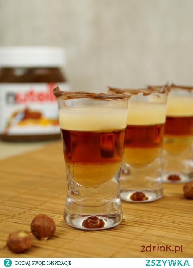 SHOT NUTELLA – PRZEPIS Składniki:  1/3 syropu orzechowego 1/3 likieru kakaowego (Creme de cacao) 1/3 wódki o smaku orzechów laskowych kilka kropli mleczka skondensowanego Nutella do dekoracji Przygotowanie:  Zaczynam od udekorowania kieliszka – obtaczam brzegi w Nutelli. Następnie wlewam kolejno składniki: syrop, likier i wódkę. Dwa ostatnie powoli, po ściankach kieliszka – najlepiej użyć nalewaka i pomóc sobie odwróconą łyżeczką. Na zakończenie dodaję kilka kropli mleczka skondensowanego – tu używam słomki, za pomocą której przenoszę mleczko z buteleczki do kieliszka. Zamiast słomki może być mała łyżeczka.