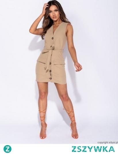 Sukienka dopasowana, zakładana w kolorze beżowym, styl safari  Dekolt zakładany głęboki, uwydatniający biust  Zapinana na ozdobne guziki  W pasie wiązanie z materiału  Z przodu kieszonki   Sukienka w kroju dopasowana, pięknie podkreślająca figurę. Sukienka idealna do stylizacji sportowej jak i eleganckiej, seksowna i oryginalna