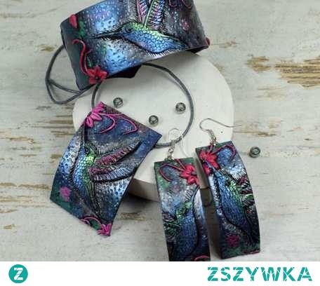 Duży, oryginalny komplet biżuterii z kolekcji KOLIBER, w skład którego wchodzi bransoletka, naszyjnik oraz długie kolczyki. Biżuteria kolorowa i przyciągająca uwagę, mieniąca wieloma odcieniami srebra, błękitu, metalicznej zieleni i dodatkiem intensywnego różu. Wykonana w całości ręcznie z profesjonalnej, trwałej glinki polimerowej. Zawieszka umieszczona została na sznurku jubilerskim o długości 55 cm wraz z zapięciem, na życzenie jego długość może zostać zmieniona.