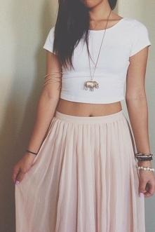 Długi naszyjnik dodaje elegancji stylizacjom. Długa różowa suknia pięknie komponuję się z białym crop topem. Stylizacja będzie nadawała się na plażę, miasto.