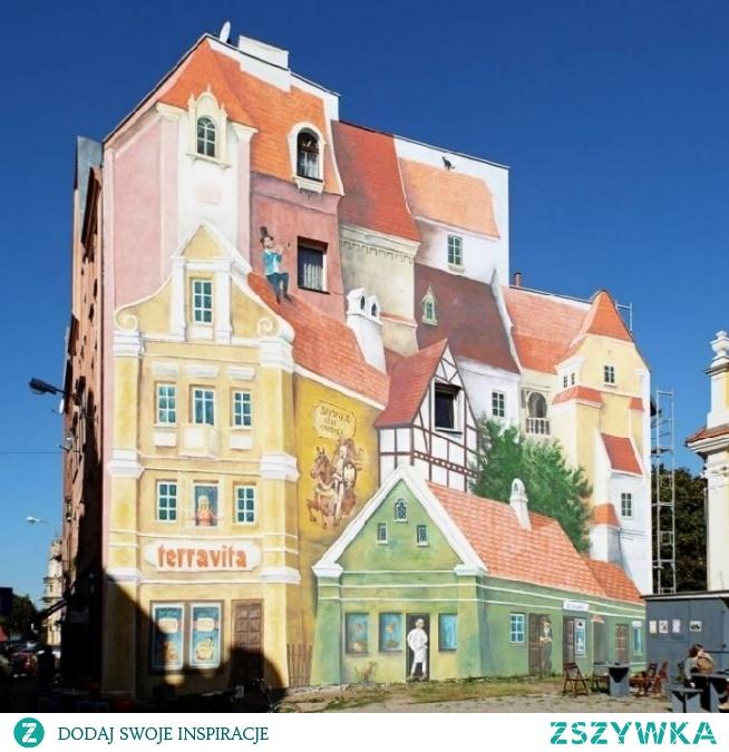 """Przechodniów poznańskiej Środki, na ścianie kamienicy na rogu ulic Śródka i Rynek Śródecki, zachwyca awangardowy, wykonany w technice 3D, mural o tajemniczej nazwie """"Opowieść śródecka z trębaczem na dachu i kotem w tle"""". Inicjatorem muralu jest Gerard Cofta, osiedlowy radny zafascynowany fotografią z lat 20. ubiegłego wieku, natomiast jego wykonawcą jest Fundacja Artystyczno-Edukacyjna Puenta, która zgłosiła mural do konkursu Centrum Warte Poznania."""
