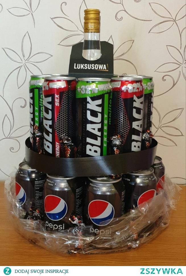 Wyjątkowy prezent w postaci tortu z udziałem ulubionego alkoholu II (pierwsza wersja na mojej tablicy)!  Moje wskazówki: - najpierw rozplanuj sobie ilość potrzebnych puszek dowolnych napojów oraz postaraj dopasować je do kształtu butelki alkoholu (w moim przypadku było to 14 puszek Pepsi jako podstawa oraz 9 puszek większego Blacka (można je znaleźć w Biedronce) oraz wódka Luksusowa 0,7l) - postaraj się wszystko zgrać kolorystycznie, ale nie jest to warunek konieczny - jako podstawkę pod puszki (tą dolną i środkową) użyłem kartonu, który przyciąłem na kształt złączonych puszek (coś na kształt kwiatka) - puszki przytwierdzamy do podstawy kartonowej za pomocą kleju na gorąco (nakładamy niewielką ilość w dwóch miejscach na dolnych krawędziach puszki) - ja dodatkowo między puszkami poprzyklejałem na klej na gorąco cukierki (dopasowałem pod kolor) - ostateczne wykończenie zależy od Ciebie, ja użyłem kolorowej tasiemki do zasłonięcia wystającego kartonu na środku tortu, całość owinąłem w celofan (kupisz w kwiaciarni) oraz zawiązałem wstążkę w miejscu szyjki butelki  Bardzo efektowny i prosty w wykonaniu prezent :)  Czas wykonania: około 40 minut Koszt: od 50 zł (ten konkretny tort kosztował mnie 77 zł)