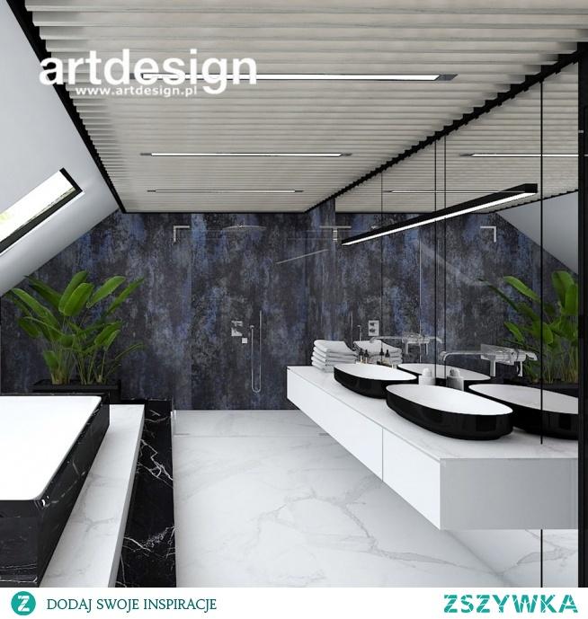 Nasza koncepcja aranżacji łazienki na poddaszu: ponadczasowa biel i czerń, oryginalny sufit wykonany z drewnianych paneli oraz kolorystyczny akcent w postaci tapety. Ściana pokryta lustrem powiększa optycznie przestrzeń, a podest z wanną dodaje elegancji.