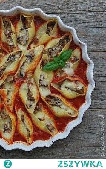 MAKARONOWE MUSZLE Z PIECZARKAMI W POMIDOROWYM SOSIE.  Składniki (na 4 porcje): - 20 dużych muszli makaronowych  nadzienie: - 2 szalotki - 50 g wędzonej szynki - 250 g pieczarek - 250 g fety - 3 łyżki natki pietruszki - 2-3 łyżki masła  sos pomidorowy: - 2 puszki pomidorów krojonych - 2 łyżki oliwy - 2 ząbki czosnku, drobno pokrojone - 1 łyżeczka oregano - 1 łyżeczka bazylii - 1 łyżeczka soli - 1/2 łyżeczki cukru - odrobina pieprzu  - ewentualnie tarty parmezan (u mnie ser grana padano) do posypania    Muszle makaronowe ugotować al dente wg instrukcji na opakowaniu.  Przygotowanie farszu: szalotki drobno posiekać, szynkę i fetę pokroić w kostkę, pieczarki w półplasterki. Szalotki zeszklić na maśle, dodać szynkę i smażyć, mieszając przez ok. 4 minuty. Dodać pieczarki i smażyć, aż powstały sos odparuje. Przestudzić. Do letniego farszu dodać natkę i fetę, wymieszać, doprawić do smaku solą i pieprzem.  Przygotowanie sosu: wszystkie składniki umieścić w rondelku. Doprowadzić do wrzenia, zmniejszyć ogień i mieszając, gotować przez 10 minut.   Gotowy sos wlać do żaroodpornej formy. Ugotowane muszle makaronowe nadziewać przygotowanym farszem i układać w formie z sosem. Całość ewentualnie posypać delikatnie tartym parmezanem.  Formę wstawić do piekarnika nagrzanego do 180 st.C i zapiekać przez około 20 minut.