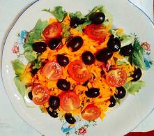 Wegańska warzywna sałatka z oliwkami czarnymi i pomidorami z sosem winegret. ...