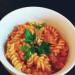 Makaron z tuńczykiem       250 g ulubionego makaronu (świderki, wstążki, nada się także spaghetti)     jedną puszkę tuńczyka w oliwie z oliwek     dwie niewielkie cebule     dwa ząbki czosnku (można dodać więcej)     pasta pomidorowa lub przecier pomidorowy     natka pietruszki     oliwa do smażenia     pieprz i sól do smaku     sok z cytryny  Przygotowanie naszego makaronu zaczynamy od obrania i pokrojenia w drobną kostkę cebuli i czosnku. Na patelni rozgrzewamy oliwę i rumienimy na złoty kolor cebulę. Po chwili dodajemy czosnek i smażymy uważając, by go nie przypalić. Kolejno dodajemy tuńczyka i po krótkim przesmażeniu dodajemy pastę pomidorową. Przyprawiamy pieprzem, solą i odrobiną soku z cytryny. Całość smażymy około 5 minut i nasz sos jest już gotowy.  W tak zwanym miedzy czasie powinniśmy nastawić na gaz garnek z osoloną wodą. Makaron gotujemy zgodnie z zaleceniami producenta, pamiętając, że najlepiej smakuje ugotowany al-dente. Gorący makaron łączymy z gorącym sosem i nasze danie jest już gotowe. Dekorujemy posiekaną pietruszką i zajadamy. Smacznego!