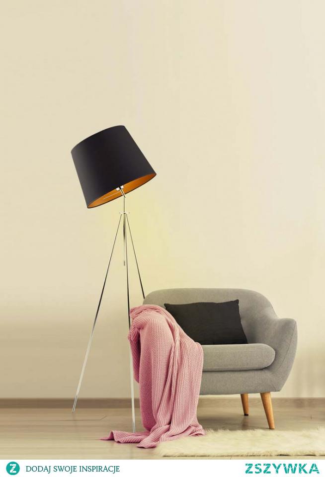 Lampa stojąca OSLO GOLD to oświetlenie charakteryzujące się niestandardową konstrukcją. Metalowy stelaż przywodzi na myśl statyw aparatu fotograficznego, jego ciekawa forma w połączeniu z prestiżową prezencją abażura, sprawia, że lampa ta w niesamowity sposób ozdabia wnętrze, wydobywając z niego wszystkie najlepsze cechy. Oświetlenie zachwyca niepowtarzalną barwą emitowanej wiązki światła, która spowodowana jest złotą powierzchnią wnętrza abażuru. Wnętrze to charakteryzuje się różnorodną fakturą, w przypadku białego abażuru jest ona połyskliwa, zaś w czarnym, zielonym, szarym i granatowym matowa. Lampa mierzy 155 cm a jej szerokość wynosi 50 cm. Zgrabna budowa oświetlenia, pozwala na umieszczenie jej w dowolnie wybranym przez nas miejscu.  Do wyboru mamy 5 kolorów abażurów (biały ze złotym wnętrzem (złoty połysk), szary stalowy ze złotym wnętrzem (złoty mat), zieleń butelkowa ze złotym wnętrzem (złoty mat), granatowy ze złotym wnętrzem (złoty mat) oraz czarny ze złotym wnętrzem (złoty mat)) jak i 6 kolorów stelaży (biały, srebrny, czarny (w standardzie), chrom, stal szczotkowana, stare złoto (dodatkowo płatne).