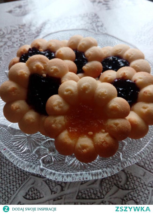 Ciasteczka maślane z marmoladą -2 szklanki mąki pszennej - 320 g -2 czubate łyżki skrobi ziemniaczanej - 50 g -kostka masła - 200 g -4 żółtka średnich jajek -pół szklanki cukru pudru - około 100 g -kilka kropel ekstraktu z wanilii -100 g marmolady lub gęstego dżemu ______ Masło utrzeć z cukrem na puszystą masę. Dodać ekstrakt z wanilii. Wymieszać. Dodawać po jednym żółtku, dokładnie wymieszać. Dodać obie mąki. Z gotowego ciasta formować niewielkie kulki, rozpłaszczyć i na środku zrobić dołek na marmoladę ( ja użyłam specjalnej maszynki do ciastek) nałożyć marmoladę. Piec 15 min. w 180°C grzanie góra dół. #domoweciasteczka #ciasteczkamaslane